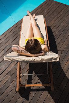 Beautiful woman in bikini relaxing by pool