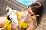 Woman reading book on sun lounger by swimming pool