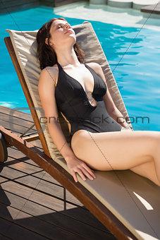 Beautiful woman in bikini relaxing by swimming pool