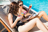 Women holding drinks by swimming pool