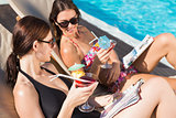 Women with drinks by swimming pool