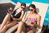 Women with drinks reading books by swimming pool