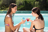 Women toasting drinks by swimming pool