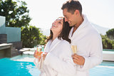 Cheerful couple with champagne flutes by swimming pool