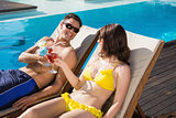 Couple toasting drinks by swimming pool