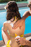 Hand applying sunscreen lotion on woman's back by swimming pool