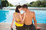 Couple sitting by swimming pool on a sunny day
