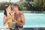 Couple with champagne flutes by swimming pool