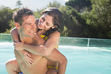 Man carrying cheerful woman by swimming pool