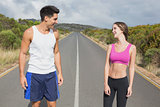 Fit couple standing on the open road