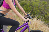 Side view of athletic woman mountain biking