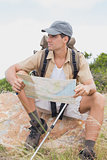 Hiking man with map on mountain terrain