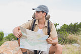 Hiking man sitting with map on mountain terrain