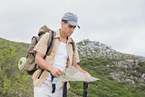 Hiking man holding map on mountain terrain