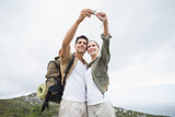 Hiking couple taking picture of themselves on mountain terrain