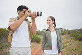 Couple taking picture on mountain terrain