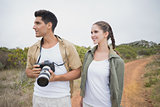 Hiking couple holding camera on mountain terrain