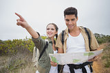 Couple with map pointing ahead on mountain terrain