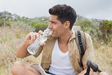 Hiking man drinking water on mountain terrain