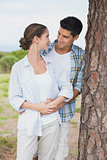 Smiling young couple standing by tree trunk