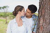 Romantic couple about to kiss by tree trunk
