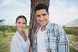 Smiling couple standing by tree trunk