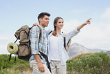 Couple pointing and smiling on country terrain
