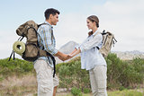 Hiking couple holding hands on mountain terrain