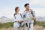 Hiking couple with map pointing ahead on mountain terrain