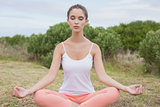 Woman sitting in lotus position on countryside landscape