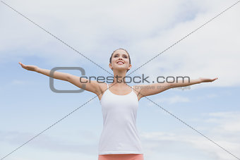 Beautiful woman with arms raised against the sky