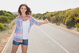 Smiling woman hitchhiking on countryside road