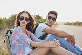 Hiking couple sitting on countryside road
