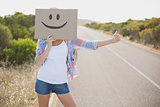 Woman with smiley face hitchhiking on countryside road