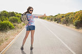 Woman hitchhiking on countryside road