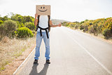 Man with smiley face hitchhiking on countryside road