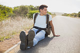 Hiking man sitting on countryside road