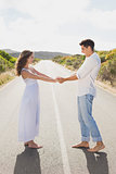 Loving couple holding hands on countryside road