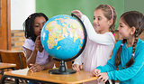 Cute pupils sitting in classroom with globe
