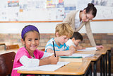 Cute pupils drawing at their desks one smiling at camera