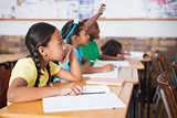 Cute pupil raising hand in classroom