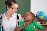 Cute pupil and teacher smiling at each other in classroom