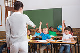 Cute pupils raising their hands in class