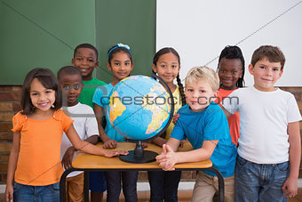 Cute pupils smiling at camera in classroom with globe