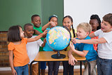 Cute pupils pointing to globe in classroom