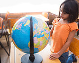 Cute little pupil looking at globe in classroom