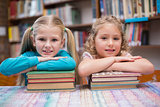 Cute pupils smiling at camera in library