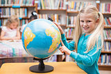 Cute pupil looking at globe in library