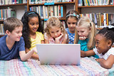 Cute pupils looking at laptop in library