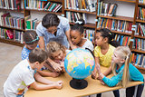 Cute pupils and teacher looking at globe in library